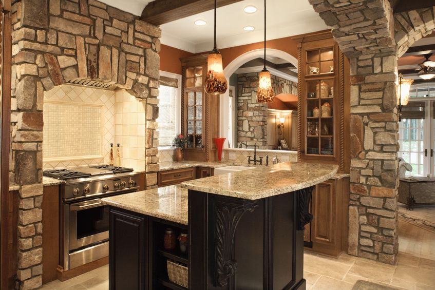 upscale kitchen interior with stone accents and wood beam ceiling.